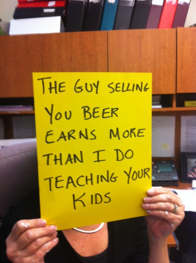 "Contract faculty member holding up a sign that says, ""The guy selling you beer earns more than I do teaching your kids."""